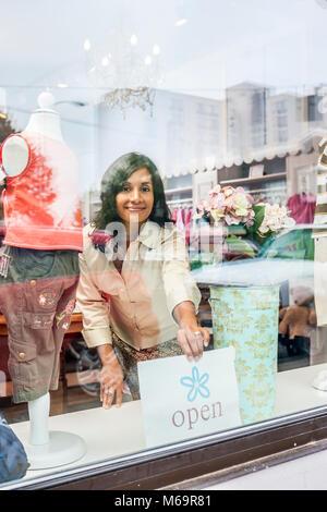 Ein Geschäft Inhaber durch die Fenster ihres Shop gesehen Drehen der offenen unterzeichnen. - Stockfoto