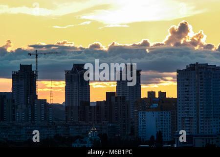 Dunkle Silhouetten der großen Stadt Häuser Bau gegen den hellen Himmel mit weißen und rosa Wolken bei Sonnenuntergang - Stockfoto