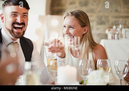 Hochzeit Gäste erfreuen sich am Tisch sitzen für die Mahlzeit. Sie reden und lachen und Wein trinken und Lager. - Stockfoto