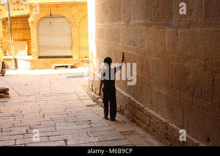Schwarze Silhouette eines kleinen Jungen zu Fuß durch einen Torbogen in einem sonnigen Straße, fegen mit einer Hand - Stockfoto