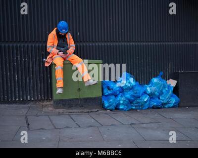 Builder, Auftragnehmer, sitzen auf der Straße Telekommunikation Cabinet, Handy, neben Müllhalden, Papierkorb, in - Stockfoto