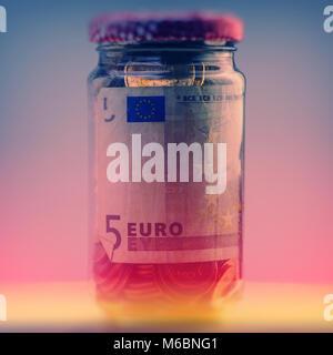 Geschlossenen Glas Glas mit Euro Münzen und Papiergeld. Nahaufnahme. Währung des Euro Union. Ticket, prüfen - Stockfoto