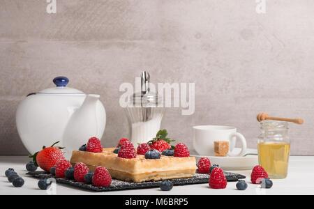Frisch gebackene Brüsseler Waffeln auf einem schwarzen Stein Teller mit frischen Erdbeeren und Heidelbeeren und - Stockfoto