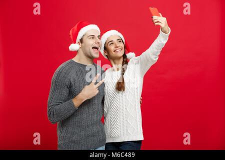 Weihnachten Konzept - Junge attraktive Paar ein selfie per Handy feiern Weihnachten - Stockfoto