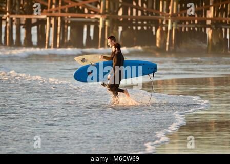 Zwei männliche Surfer, die surfbretter bei Sonnenuntergang, Wandern am Strand mit Pacific Beach Crystal Pier im - Stockfoto