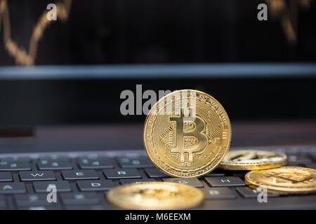Spielen mit cryptocurrency: Mehrere bitcoins auf einem Laptop Tastatur - Stockfoto
