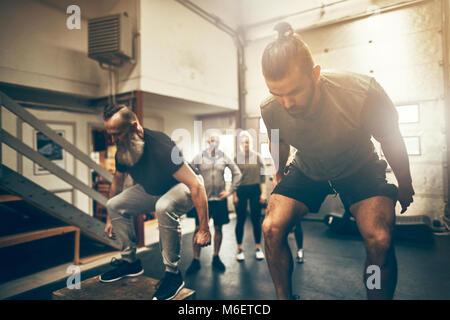 Zwei passen Männer Box springt bei einem Fitnessstudio Klasse mit Freunden beobachten im Hintergrund - Stockfoto