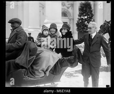 First Lady Grace Coolidge (Mitte), von Chief White House Usher Ike Hoover sitzt (rechts), genießt eine Schlittenfahrt - Stockfoto