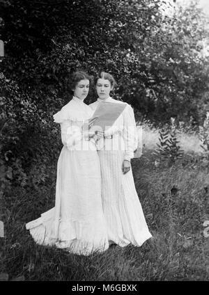 Schwestern stellen in den Schatten, während ein Magazin des Tages lesen, Ca. 1900. - Stockfoto