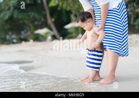 Asiatische Kleinkind Baby Junge mit der Mutter, der seine ersten Schritte auf dem Sand in der Nähe des Bank - Stockfoto