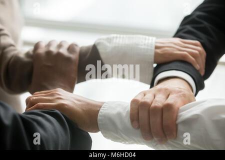 Vier multirassischen Geschäftsleute halten jedes anderen Handgelenken, Clo - Stockfoto