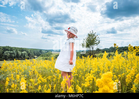 Süße kleine lachende Mädchen zu Fuß im Bereich der Sommer gelb Blumen. Glückliche Kindheit - Stockfoto