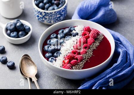 Smoothie Schale mit frischen Himbeeren, Heidelbeeren, Kokosraspeln und Chia Samen. Grauen Stein Hintergrund. - Stockfoto