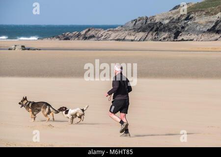 Ein Mann läuft mit seinen Hunden auf Crantock Beach in Newquay Cornwall.
