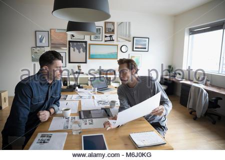 Männliche Fotoeditoren überprüfung Foto Beweise im Büro treffen - Stockfoto