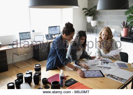 Weibliche foto Editoren mit digitalen Tablet überprüfung Foto Beweise im Büro - Stockfoto