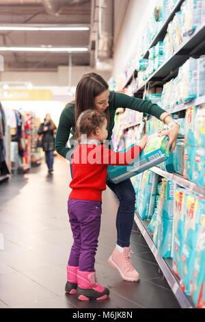 d116d0fee17b61 ... Kleines Mädchen Auswahl Windeln im Supermarkt mit ihrer Mama. -  Stockfoto