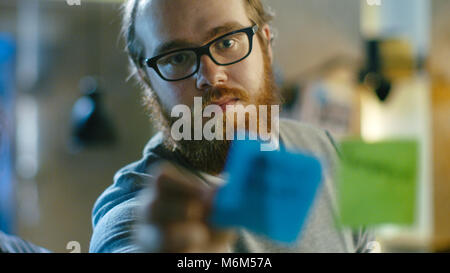 Männliche Designer Plan sein nächstes Projekt auf einer Glaswand mit Haftnotizen skizzieren. - Stockfoto