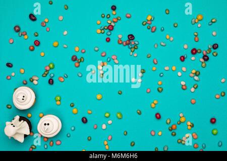 Blick von oben auf die bunten Bonbons und Halloween gespenst Cupcakes auf Blau - Stockfoto
