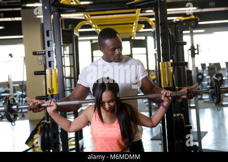 Frau heben Langhantelstange mit Trainer im Fitnessraum - Stockfoto