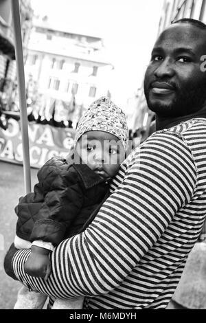 Savona, Italien - Oktober 15, 2017: Junge afrikanische Vater mit Tochter in den Armen während einer antifaschistischen - Stockfoto