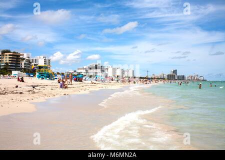 Blick auf Miami South Beach während sonniger Tag. Kleine Wellen schlagen Sandstrand als Menschen Sonnenschein genießen. - Stockfoto