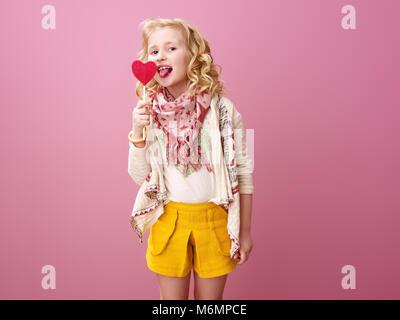 Rosa Stimmung. Lächeln moderne Kind mit Welligem blonden Haar isoliert auf rosa Hintergrund lecken herzförmige Lollipop - Stockfoto