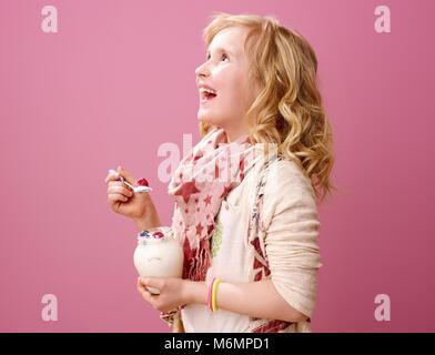 Rosa Stimmung. Glücklich moderne Mädchen mit Welligem blonden Haaren auf rosa Hintergrund mit Bauernhof bio Joghurt - Stockfoto
