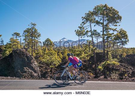 Radfahrer auf der Straße vorbei an schneebedeckten Teide - Stockfoto