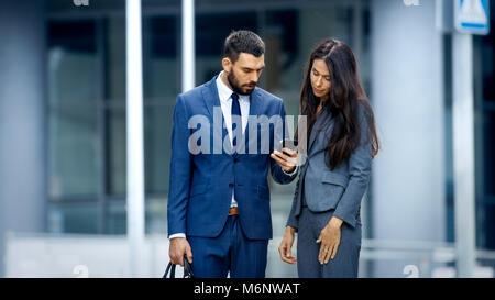 Business-frau und Geschäftsmann Verwendung des Smartphones und Sprechen auf der geschäftigen Großstadt-Straße. Beide - Stockfoto