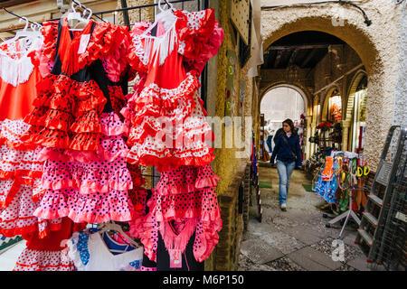 Eine junge Frau geht vorbei an traditionellen Flamenco Kleider in der touristischen Alcaiceria souvenirs Markt. - Stockfoto