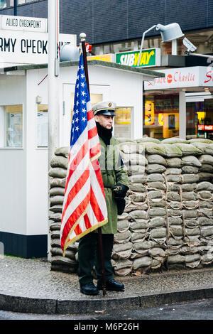 Ein Mann hält eine amerikanische Flagge Wacht am Checkpoint Charlie, Berlin, Deutschland - Stockfoto