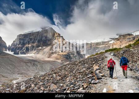 Wanderer auf Ebene der Sechs Gletscher Trail, Geröll bedeckten Pisten, Mount Lefroy Links, Mount Victoria in Wolken, - Stockfoto