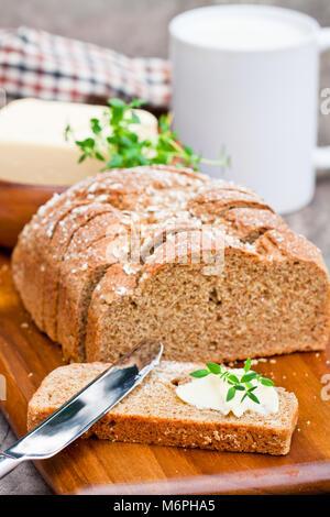 Scheiben Irischen stoneground Soda Brot mit Butter und Thymian auf dem hölzernen Tisch
