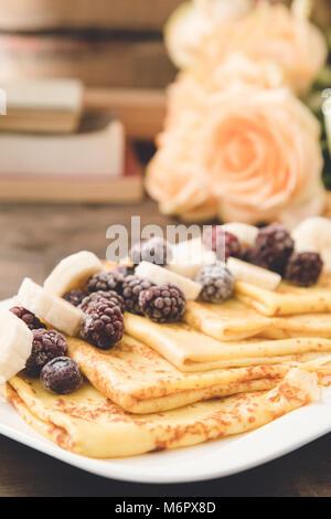 Pfannkuchen mit Banane und Gefrorene Beeren auf dunklem Hintergrund. Crepes mit Bananen und Früchte - Stockfoto