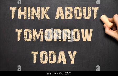 Heute schon an morgen denken! - Weibliche Hand Schreiben von Text auf der Tafel. - Stockfoto