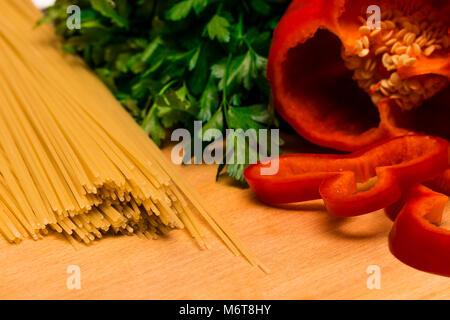 Frische Zutaten zum Kochen: Pasta und Pfeffer und Petersilie auf Holz- hintergrund Tabelle. - Stockfoto
