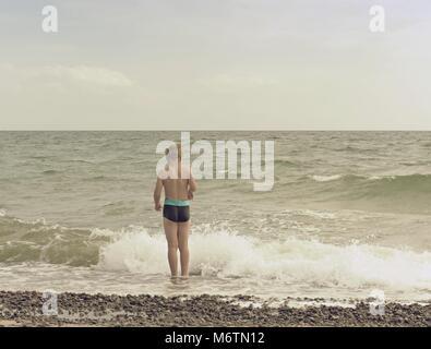 Blonde Haare junge Aufenthalt im kalten Meer tide. Kid auf steinigen Strand mit schäumenden Wellen. Windigen Tag, - Stockfoto