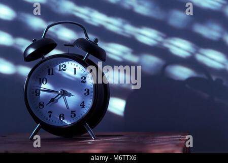 Metallische Wecker Auf Dunklen Nachttisch · Wecker Auf Nachttisch Im Schlafzimmer  Tickende Am Frühen Morgen Mit Dem Sonnenlicht Und Schatten An Der