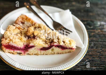 Stück süße Torte mit Dessert Gabel auf einem Teller auf einem hölzernen Oberfläche im Cafe - Stockfoto