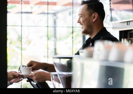 Barkeeper serviert einen kurzen Espresso zum Kunden - Stockfoto
