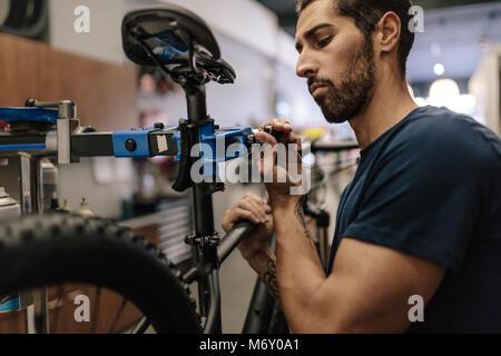 Arbeitnehmer Instandsetzung ein Fahrrad an der Werkstatt. Mann zur Festsetzung ein Fahrrad zu einem Betrieb stehen - Stockfoto