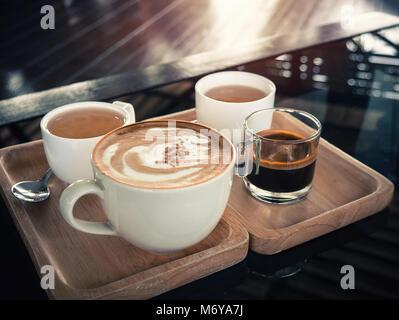 Tassen Cappuccino auf hölzernen Hintergrund. grün Keramik Tassen. vintage Ton Farben Stil. Tasse Kaffee Konzept. Stockfoto