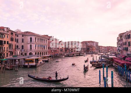 Bunte rosa Sonnenuntergang in der Dämmerung über den Canal Grande, Venedig, Italien wie von der Rialto Brücke über Riva del Vin gesehen mit Gondeln und Bootsverkehr und t