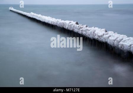 07 März 2018, Deutschland, Boltenhagen: eine dicke Schicht von Eis bedeckt Buhnen an der Ostsee Küste. (Mit Langzeitbelichtung) - Stockfoto