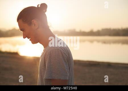Profil von stattlicher Mann lächelnd zeigt Zähne im Park, auf dem See bei Sonnenaufgang. Portrait von athletischen - Stockfoto