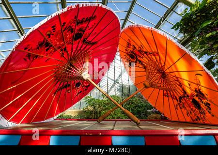 Zwei hellen Rot und Orange oriental style Sonnenschirme nebeneinander auf einem hölzernen Kasten - Stockfoto