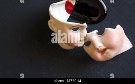 Broken doll Gesichter und Blut isoliert auf grunge schwarzer Hintergrund mit Blut spritzt. Konzeptionelle Bild von - Stockfoto