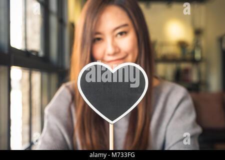 Eine schöne asiatische Frau mit einem leeren Herzen Form Tafel mit Gefühl glücklich und verliebt - Stockfoto