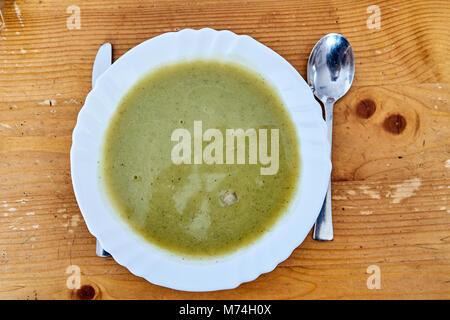 Zucchini Suppe in einer weißen Platte auf einem Holztisch - Stockfoto
